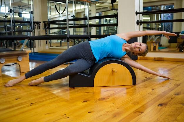 Mulher apta fazendo pilates em arco
