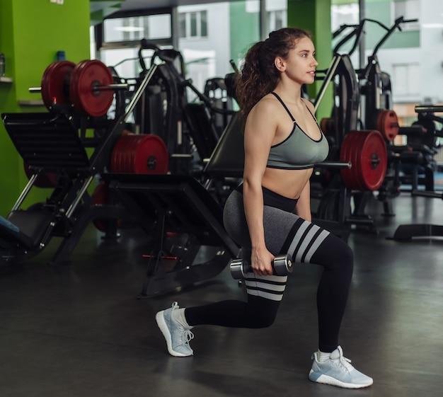 Mulher apta jovem arremete com halteres. treinamento de pernas na academia com pesos livres. estilo de vida saudável