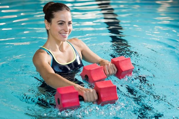 Mulher apta malhando com halteres de espuma na piscina