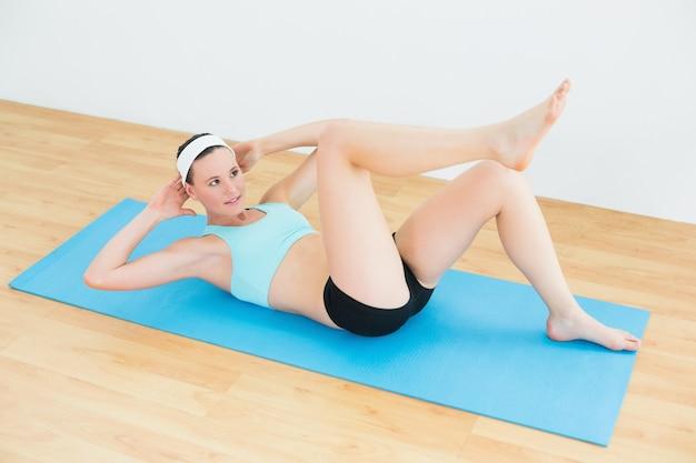 Mulher apta para desportivo fazendo assentos na esteira de exercícios