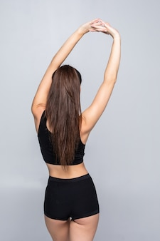 Mulher apta que estica suas costas isoladas