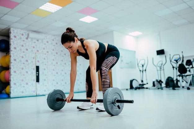 Mulher apta que faz o exercício do levantamento de peso no gym.