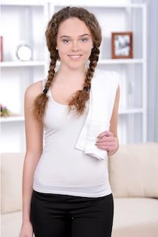 Mulher apta que guarda uma toalha em seu ombro após o exercício.