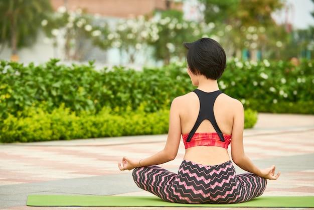 Mulher apta que treina ioga ao ar livre