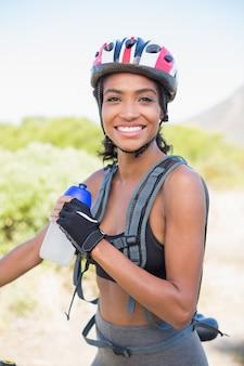 Mulher apta que vai de bicicleta segurando garrafa de agua