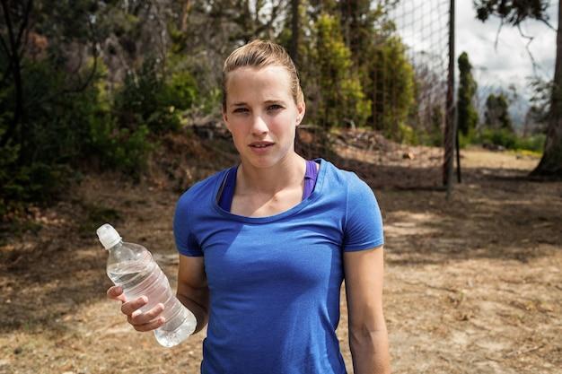 Mulher apta segurando uma garrafa de água no campo de treinamento