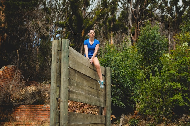 Mulher apta sentada sobre um obstáculo de parede de madeira