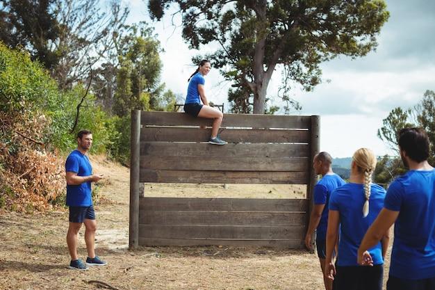 Mulher apta sentada sobre uma parede de madeira durante uma pista de obstáculos