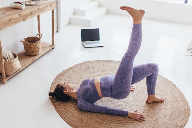 Mulher apta treina em casa e exerce ponte de glúteo.