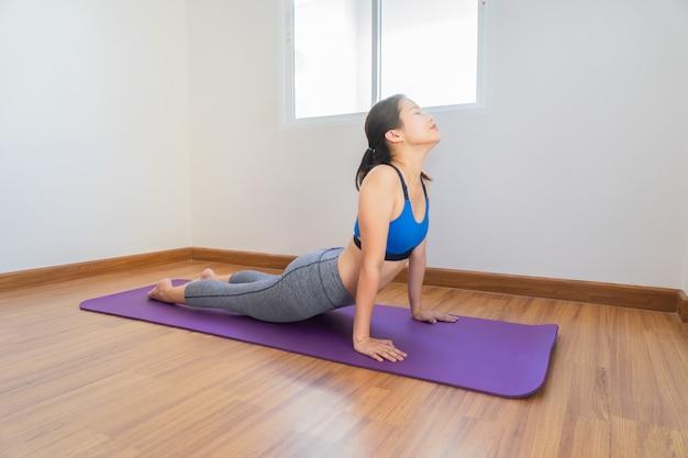 Mulher aquecer ou yoga na esteira de treinamento na sala em casa