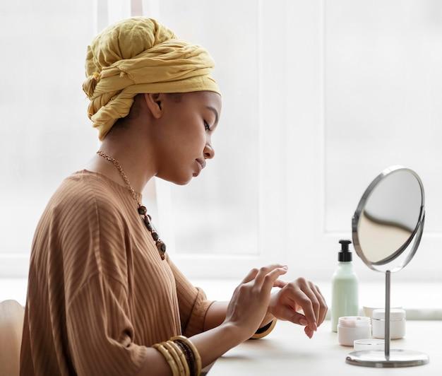 Mulher árabe aplicando creme nas mãos. tratamento de beleza