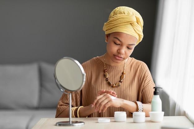 Mulher árabe aplicando creme no rosto. tratamento de beleza