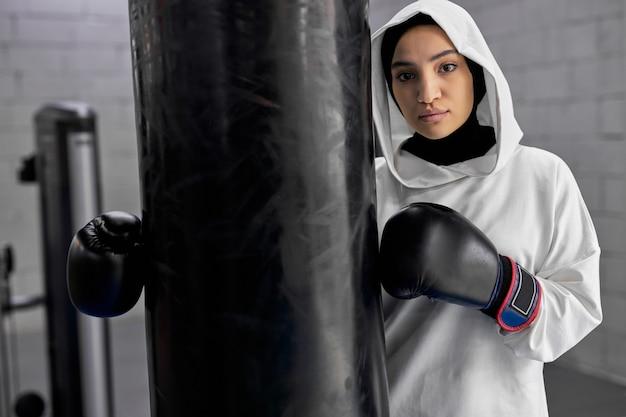 Mulher árabe apta a fazer uma pausa após o treino de boxe duro, mulher muçulmana fica perto de um saco de pancadas, posando para a câmera, no ginásio. mulher em hijab