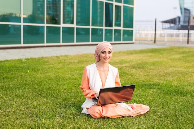 Mulher árabe bem-sucedida e empresária árabe com laptop usando hijab e trabalhando em um laptop no parque