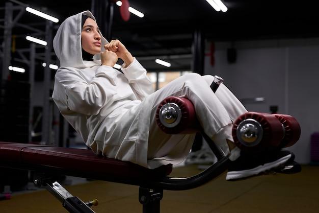 Mulher árabe bombeia abdominais no centro de fitness, deitada no equipamento, concentrada no treino, sozinha. conceito de esporte e crossfit