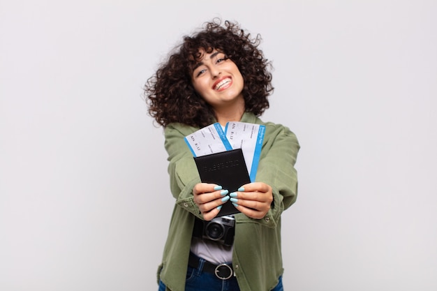 Mulher árabe bonita com um avião e bilhetes de embarque. conceito de viagens