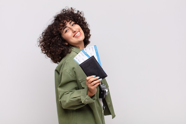 Mulher árabe bonita com um avião e bilhetes de embarque.