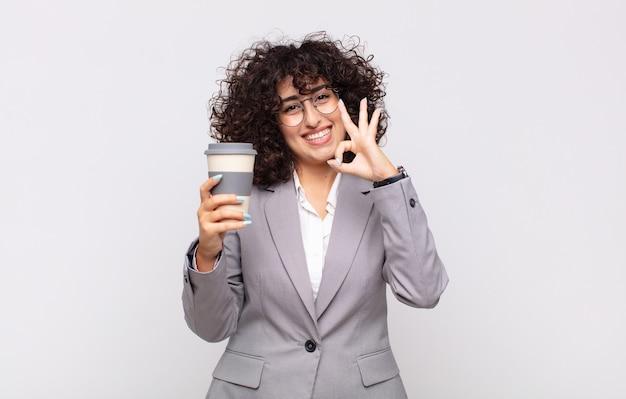 Mulher árabe bonita com um café para viagem