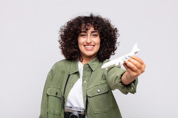 Mulher árabe bonita com um modelo de avião. conceito transversal
