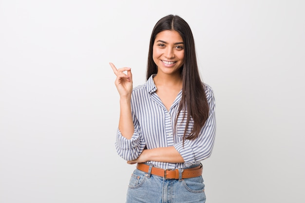 Mulher árabe bonita dos jovens que sorri alegremente apontando com dedo indicador afastado.
