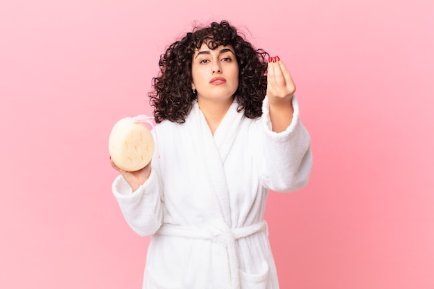 Mulher árabe bonita fazendo capice ou gesto de dinheiro, dizendo para você pagar vestindo um roupão de banho e segurando uma esponja