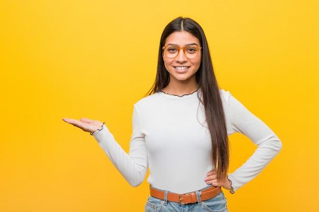 Mulher árabe bonita nova contra um fundo amarelo que mostra um espaço da cópia em uma palma e que guarda uma outra mão na cintura.
