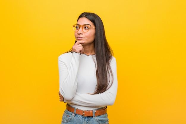 Mulher árabe bonita nova contra uma parede amarela que olha lateralmente com expressão duvidosa e cética.