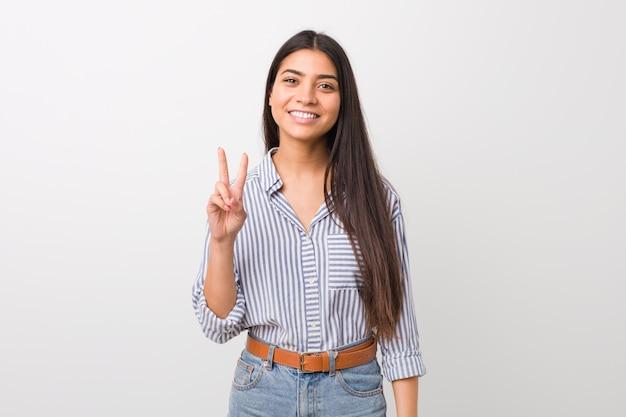 Mulher árabe bonita nova que mostra o sinal da vitória e que sorri amplamente.