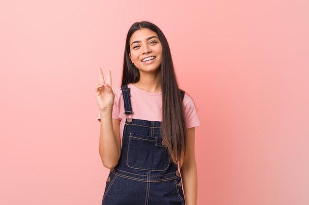 Mulher árabe bonita nova que veste um dungaree das calças de brim alegre e despreocupada mostrando um símbolo de paz com os dedos.
