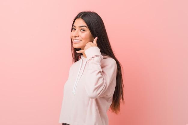 Mulher árabe bonita nova que veste um olhar ocasional do esporte que mostra um gesto de chamada de telefone móvel com os dedos.