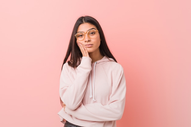 Mulher árabe bonita nova que veste um olhar ocasional do esporte que seja furado, desgastado e precise um dia do relax.