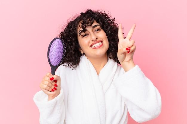 Mulher árabe bonita usando roupão de banho e segurando uma escova de cabelo
