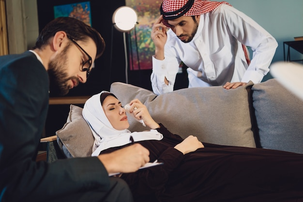 Mulher árabe com marido na recepção do psicólogo