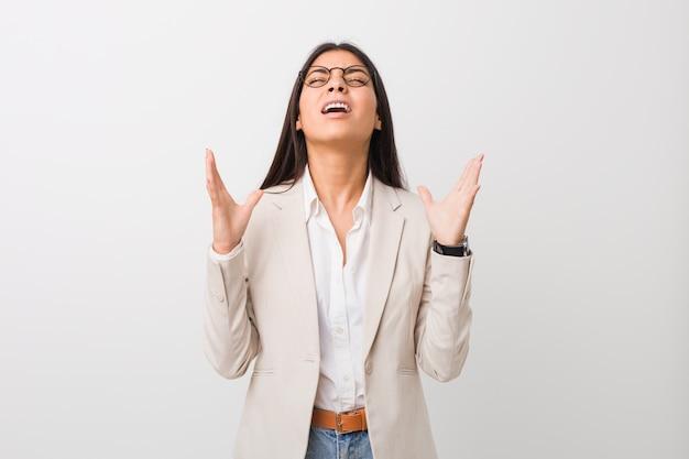 Mulher árabe de negócios jovem isolada contra um fundo branco, gritando para o céu