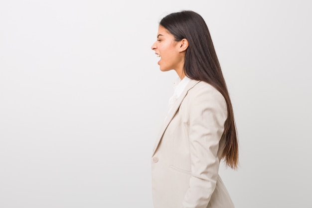Mulher árabe de negócios jovem isolada no branco gritando para um espaço de cópia
