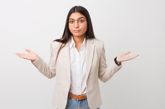 Mulher árabe do negócio novo isolada contra um branco que duvida e que encolhe os ombros em questionar o gesto.