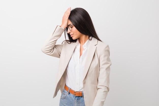 Mulher árabe do negócio novo isolada contra um fundo branco que esquece algo, batendo na testa com palma e fechando os olhos.