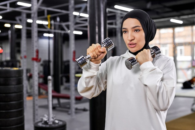 Mulher árabe em hijab branco, exercitando-se com halteres no ginásio, desfrutando de um estilo de vida saudável e ativo, concentrado no treino, copie o espaço. esporte, fitness, conceito de treinamento