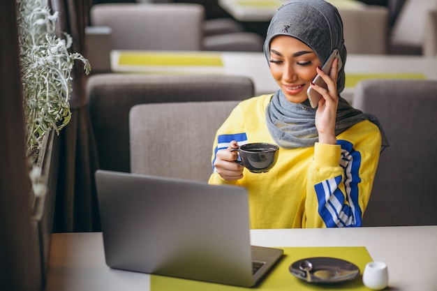 Mulher árabe em hijab dentro de um café trabalhando no laptop