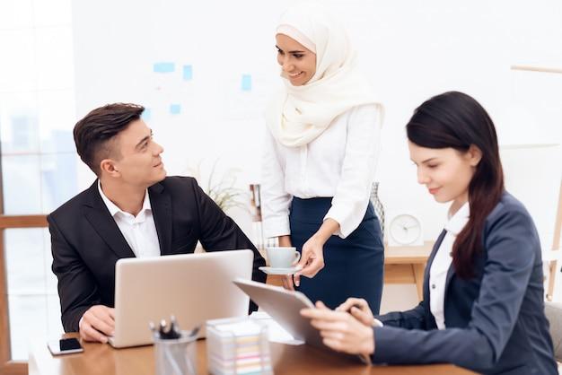 Mulher árabe em hijab trabalha no escritório juntos.