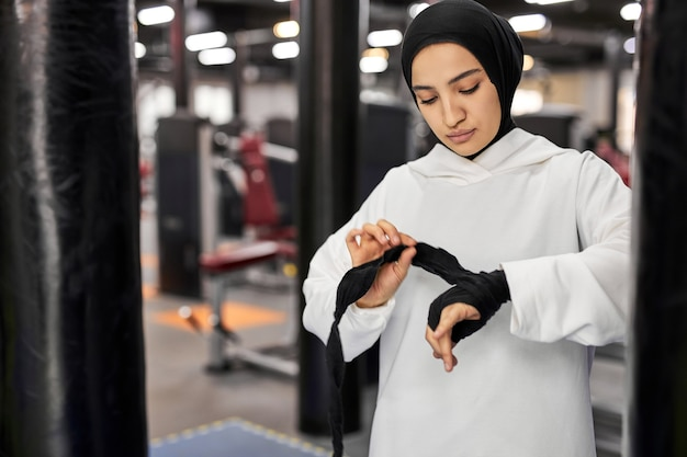 Mulher árabe em roupas esportivas muçulmanas amarrar bandagens elásticas nas mãos. mulher forte está se preparando para treinar, boxe sozinha. na academia