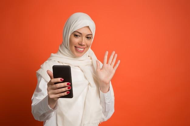 Mulher árabe feliz em hijab com telefone celular fazendo selfie.
