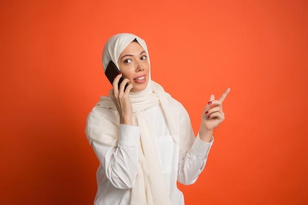 Mulher árabe feliz em hijab com telefone celular.