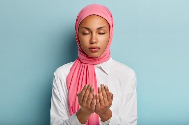 Mulher árabe fiel de pele escura mantém as mãos em gesto de oração, pede a deus por boa saúde, acredita no bem-estar tem a cabeça velada, usa camisa branca mantém os olhos fechados desfruta de uma atmosfera pacífica