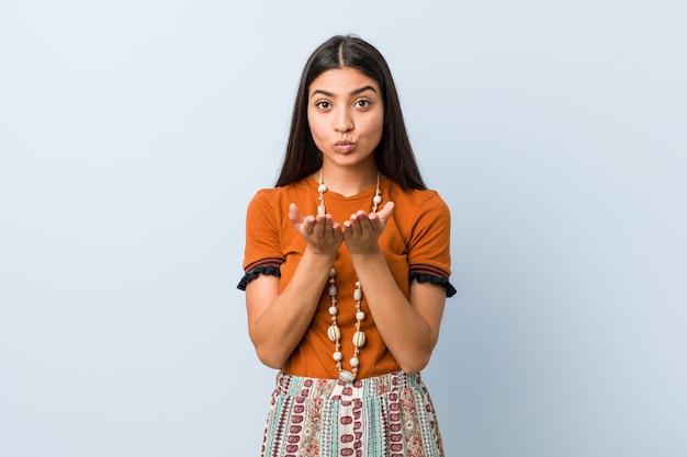 Mulher árabe jovem dobrar os lábios e segurando as palmas para enviar o beijo do ar.
