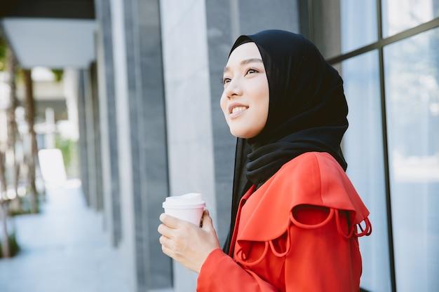 Mulher árabe muçulmana asiática jovem sorridente segurando uma xícara de café em pé retrato