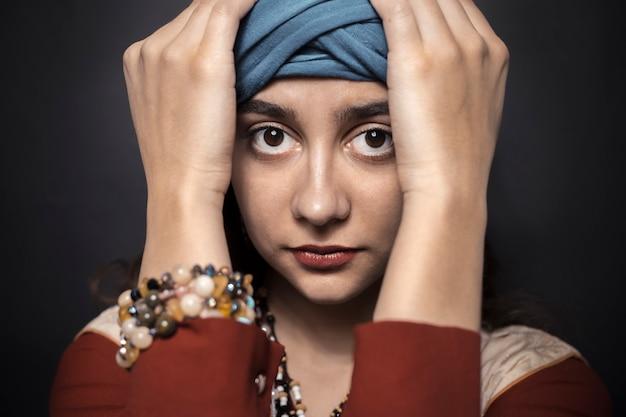 Mulher árabe no turbante em um fundo preto.