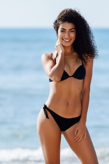 Mulher árabe nova com corpo bonito no roupa de banho que sorri em uma praia tropical.