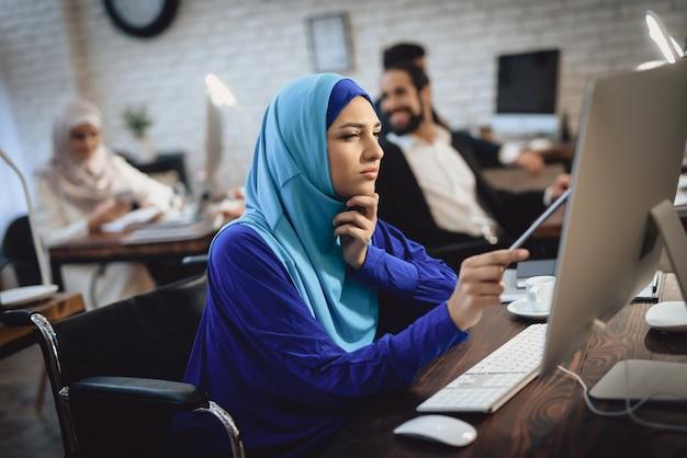 Mulher árabe nova na menina deficiente atenta do pc.