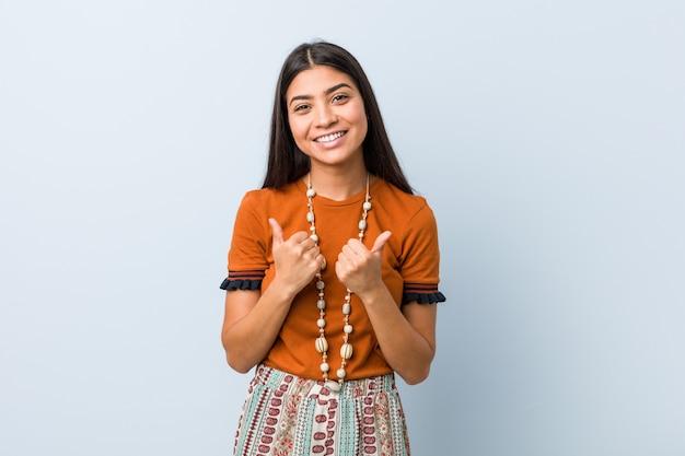 Mulher árabe nova que aumenta ambos os polegares acima, sorrindo e seguro.